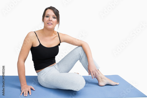 Portrait of young woman in sportswear sitting on yoga mat