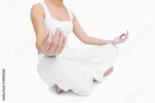 Midsection of young woman sitting in lotus position