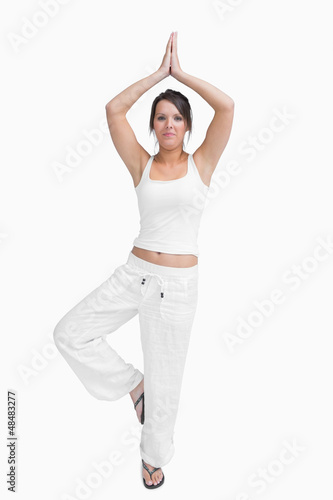 Portrait of woman in sportswear doing the tree pose