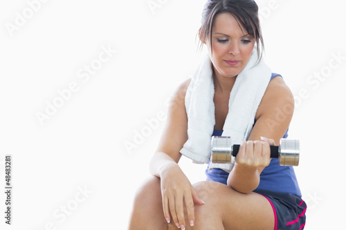 Young woman sitting and exercising with dumbbell