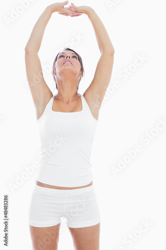 Young woman in sportswear holding hands up together