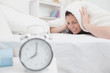 Woman covers ears with sheet as alarm clock rings