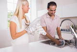 Happy couple washing dishes together