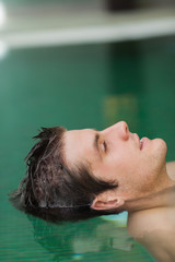 Relaxed man floating in pool