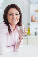 Young woman with glass of water in the kitchen