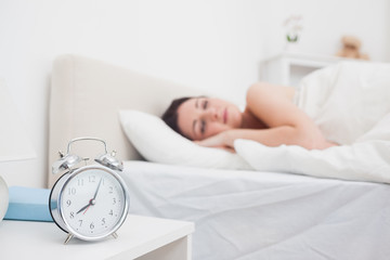 Woman sleeping in bed with focus on alarm clock