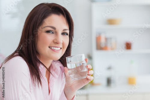 Close-up portrait of woman with glass of water