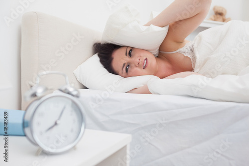 Woman covers ears with pillow as alarm clock rings