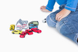 Close-up of boy playing with playhouse and toy cars
