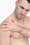 Close-up of shirtless man with shoulder pain