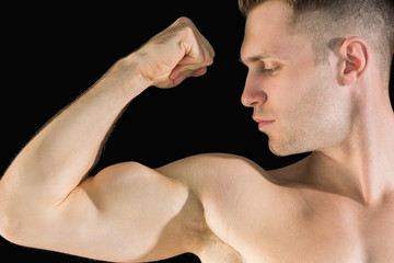 Close-up of young man flexing muscles