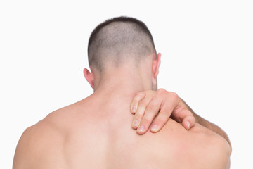 Rear view of shirtless man with neck pain