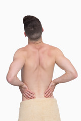 Rear view of shirtless man with back pain