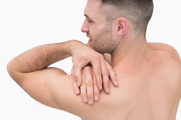 Rear view of shirtless man with shoulder pain