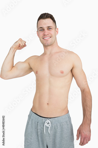 Portrait of shirtless young man flexing muscles