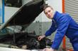 Confident mechanic checking car engine oil