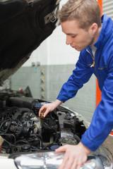Mechanic checking car engine oil