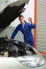 Mechanic by car making ok sign