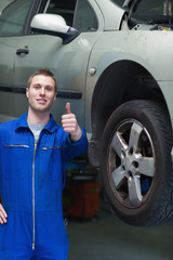 Car mechanic gesturing thumbs up