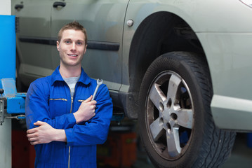 Male mechanic standing by car