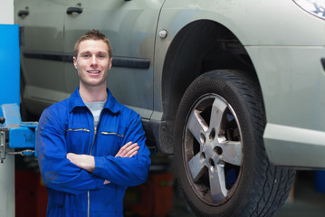 Confident male mechanic standing by car