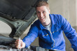 Male mechanic working on automobile engine