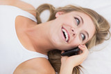 Happy woman phoning lying on the bed