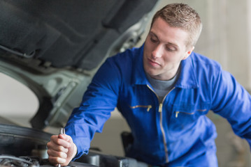 Auto mechanic working on car