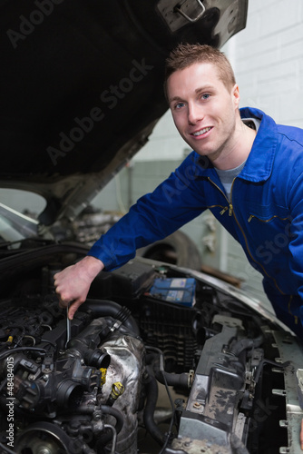 Young mechanic repairing car engine