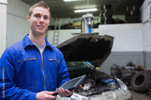 Male mechanic with digital tablet at garage