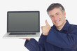 Mechanic with laptop showing thumbs up sign