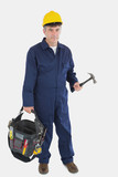 Mature mechanic carrying tool bag