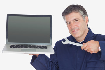 Mature mechanic holding wrench and laptop