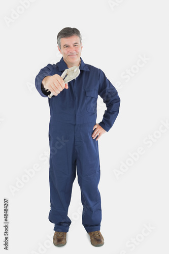 Mechanic with hand on waist holding vise grip