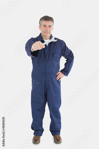 Confident mechanic holding out wrench