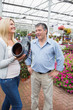 Couple laughing at flower pot shaped like boot