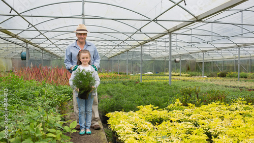 Gardener and granddaughter holding a large potted plant