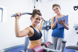 Smiling woman on weights machine with trainer