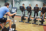 Male instructor teaches spinning class