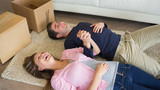 Laughing couple lying on floor with moving boxes