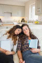 Girls sleeping while holding tablet computers