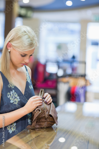 Woman standing at the counter while searching in her bag