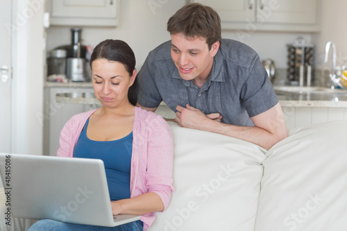 Woman using laptop with man looking on