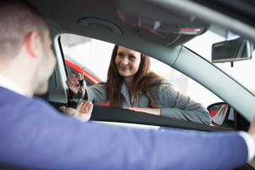 Woman giving car keys to a customer