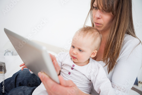 Serious woman holding her baby while using a tablet pc