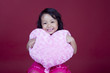 Cheerful girl holding pink heart