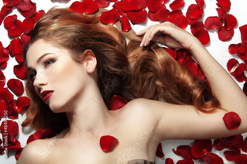 Beautiful girl on rose petals