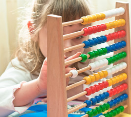 Girl contemplates the basics of arithmetic on his abacus.