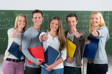 motivierte schülergruppe zeigt daumen hoch