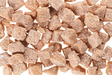 Many brown lump cane sugar cubes , food background